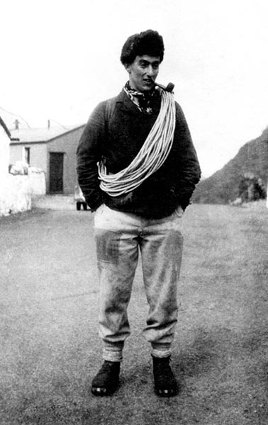 Black and White image of Jack Longland, with rope over his shoulder dressed for climbing